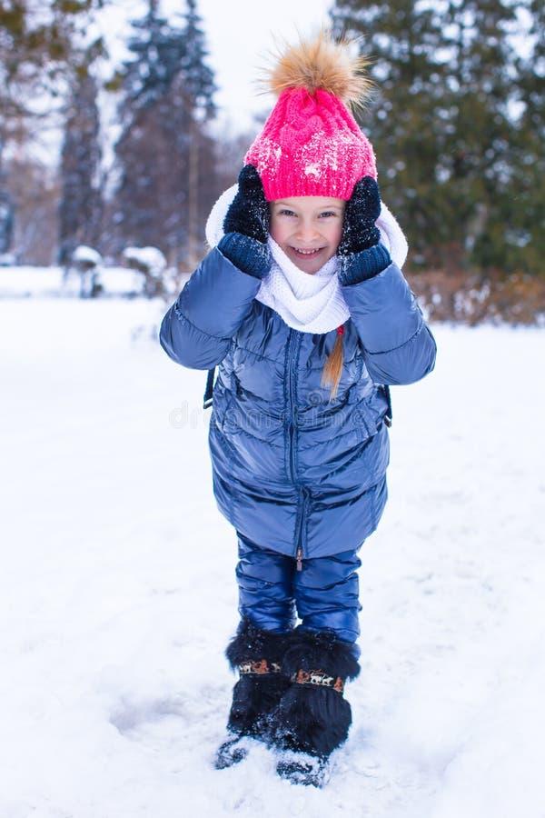 Retrato de la pequeña muchacha feliz en la nieve soleada foto de archivo
