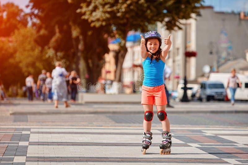 Retrato de la pequeña muchacha feliz linda rollerblading a través de las calles de la ciudad en el día de verano risueno caliente fotos de archivo