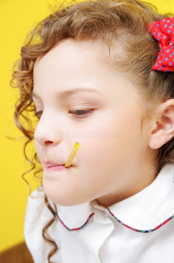 Retrato de la pequeña muchacha rizada con el termómetro en boca foto de archivo