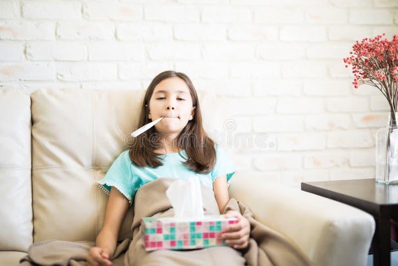 Retrato de la pequeña muchacha rizada con el termómetro en boca imagenes de archivo