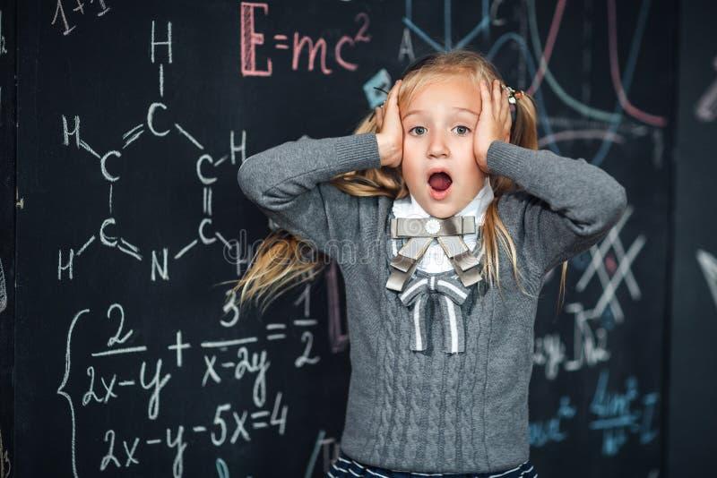 Retrato de la pequeña muchacha rubia, asiendo su cabeza pizarra con fórmulas de la escuela en el fondo, foto del concepto fotos de archivo