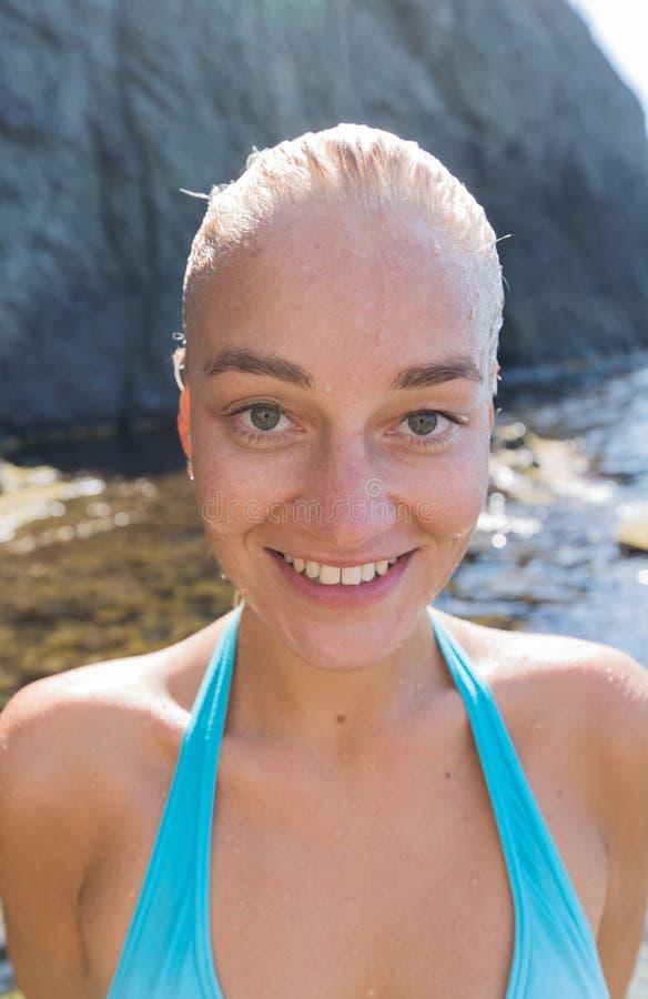 Retrato de la persona femenina atractiva con el pelo slicked mojado contra la playa rocosa fotos de archivo libres de regalías