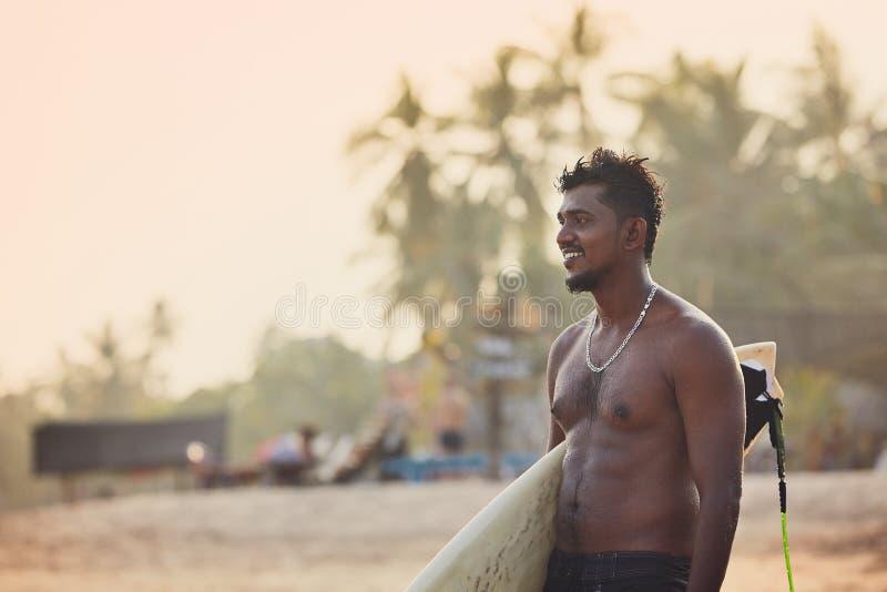Retrato de la persona que practica surf en la puesta del sol imagen de archivo libre de regalías