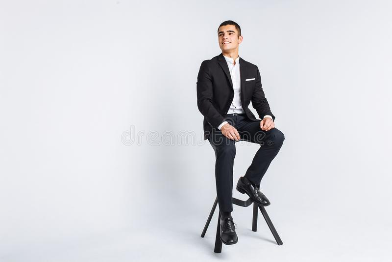 Retrato de la presentación hermosa en un estudio, fondo blanco, hombre de negocios elegante, hombre elegante que se sienta en una fotos de archivo libres de regalías