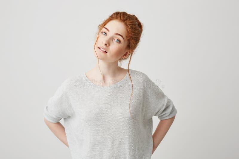 Retrato de la presentación sonriente de la muchacha blanda hermosa del pelirrojo mirando la cámara sobre el fondo blanco imagen de archivo