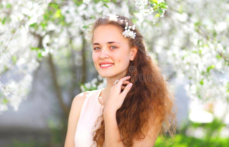 Retrato de la primavera de la chica joven hermosa con el pelo rizado en jardín floreciente imágenes de archivo libres de regalías