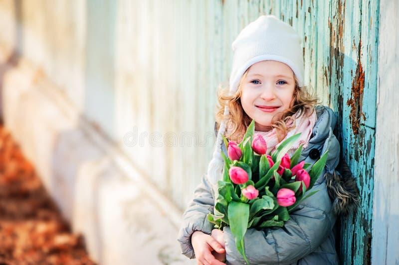 Retrato de la primavera de la muchacha feliz del niño con el ramo de los tulipanes para el día de la mujer fotos de archivo libres de regalías