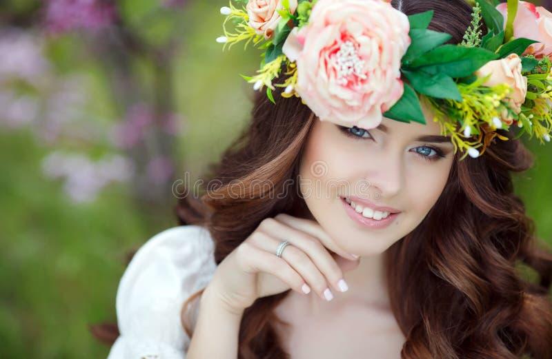 Retrato de la primavera de una mujer hermosa en una guirnalda de flores fotografía de archivo
