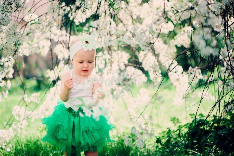 Retrato de la primavera del bebé lindo en falda verde que disfruta del paseo al aire libre en jardín floreciente foto de archivo libre de regalías