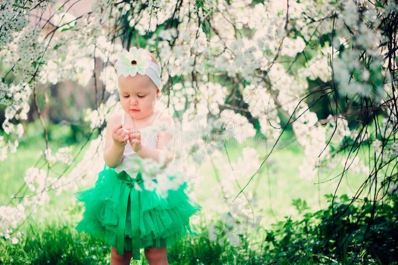 Retrato de la primavera del bebé lindo en falda verde que disfruta del paseo al aire libre en jardín floreciente foto de archivo