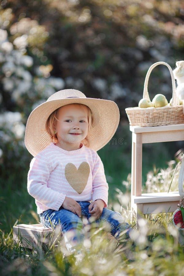Retrato de la primavera de una niña encantadora que camina en un parque florecido imagenes de archivo