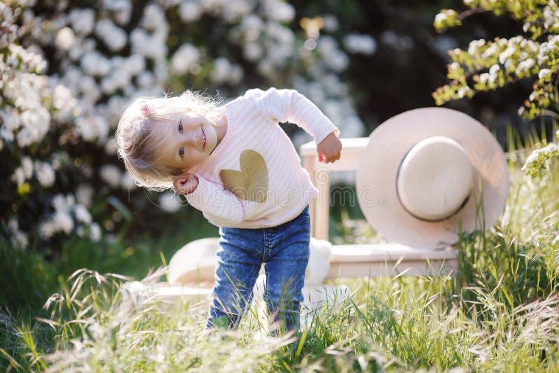 Retrato de la primavera de una niña encantadora que camina en un parque florecido imagen de archivo libre de regalías