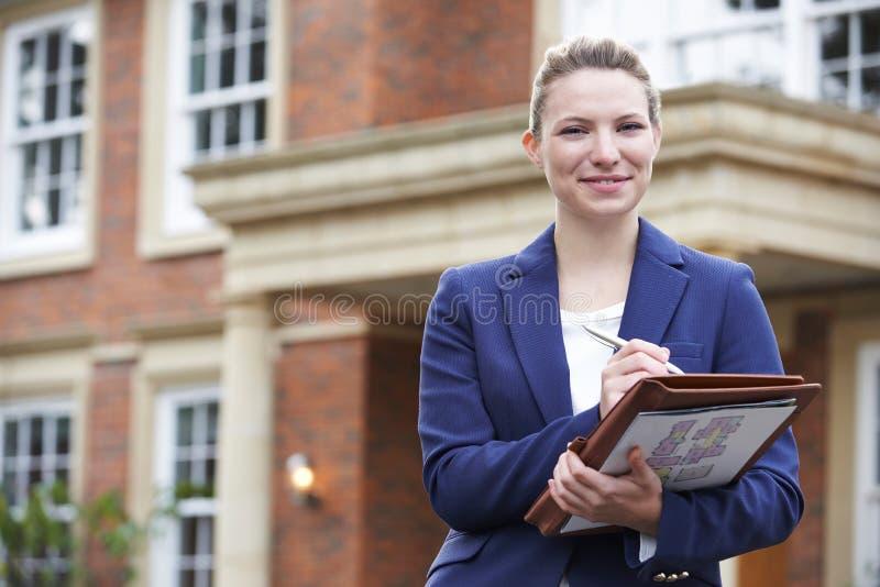 Retrato de la propiedad residencial del exterior derecho femenino del agente inmobiliario imagenes de archivo