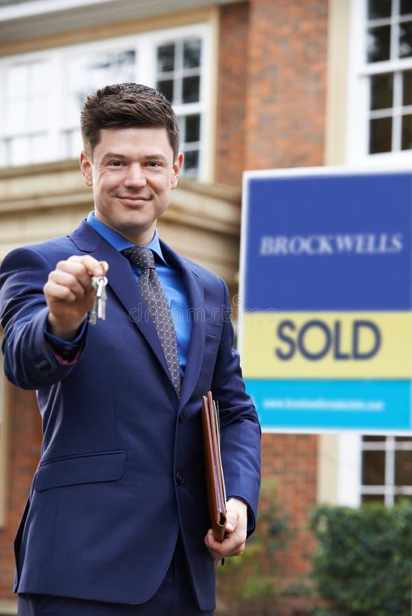 Retrato de la propiedad residencial H del exterior derecho masculino del agente inmobiliario fotografía de archivo