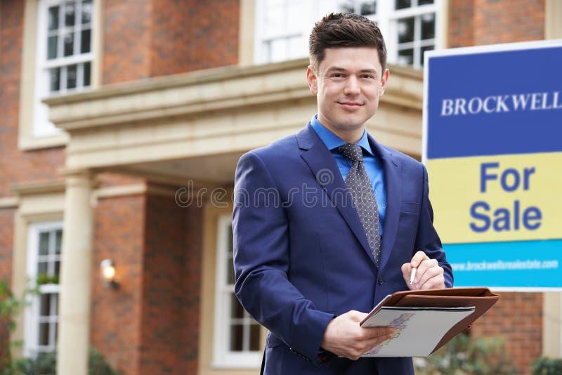 Retrato de la propiedad residencial W del exterior derecho masculino del agente inmobiliario fotos de archivo