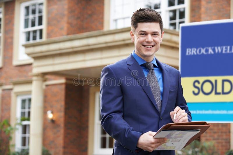 Retrato de la propiedad residencial W del exterior derecho masculino del agente inmobiliario foto de archivo