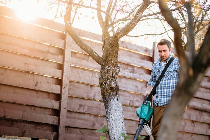 retrato de la puesta del sol del hombre que goza que trabaja en jardín, usando ventilador de hoja y vacío imágenes de archivo libres de regalías