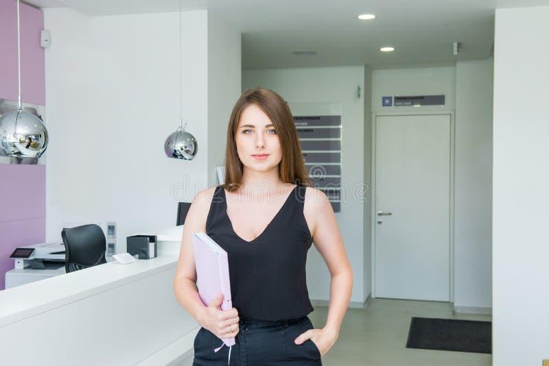 Retrato de la señora atractiva y confiada que sostiene su cuaderno y que se coloca en la oficina de negocios Pasillo Empresario j fotos de archivo libres de regalías