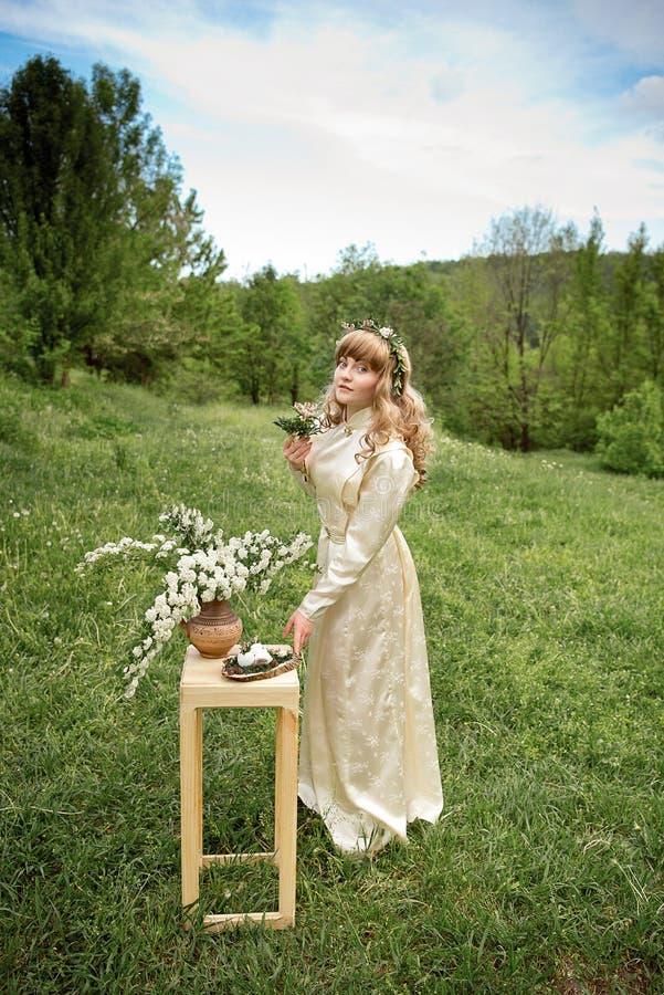 Retrato de la señora hermosa con la guirnalda en la cabeza en campo verde al aire libre fotografía de archivo