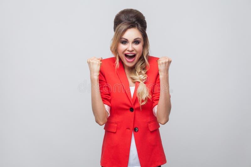 Retrato de la señora hermosa feliz emocionada del negocio con el peinado y el maquillaje en chaqueta de lujo roja, colocándose en fotos de archivo libres de regalías