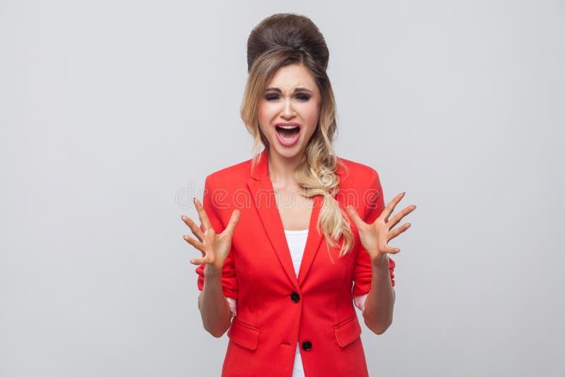 Retrato de la señora hermosa nerviosa del negocio con el peinado y el maquillaje en chaqueta de lujo roja, colocación, mirando la fotografía de archivo