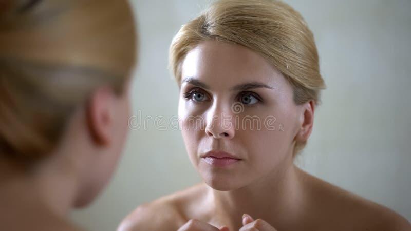 Retrato de la señora hermosa que mira la reflexión de espejo, efecto poner crema antienvejecedor imagenes de archivo