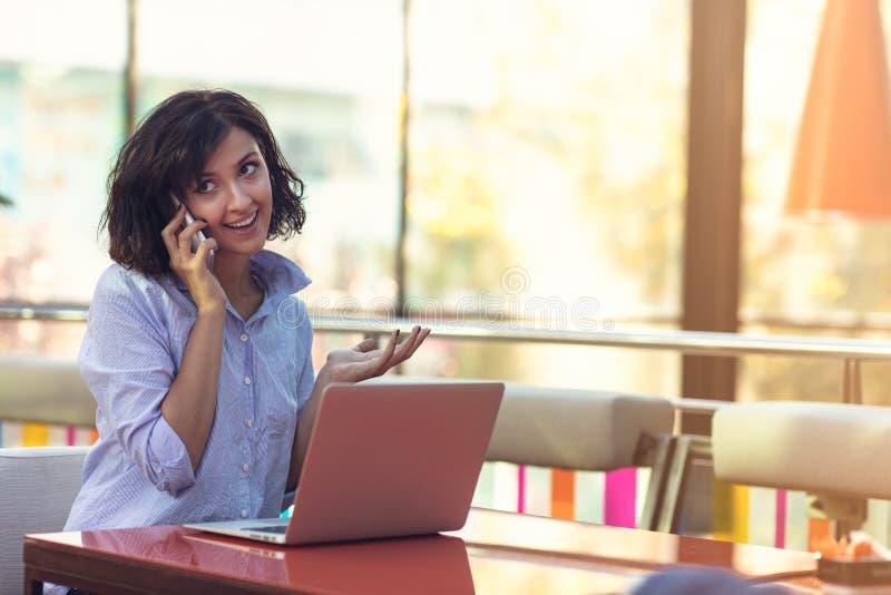 Retrato de la señora joven alegre que se sienta en el café con el teléfono móvil imagen de archivo libre de regalías