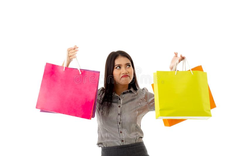 Retrato de la señora joven asiática rodar sus ojos, sosteniendo bolsos que hacen compras coloridos La mujer de negocios con terap imagenes de archivo