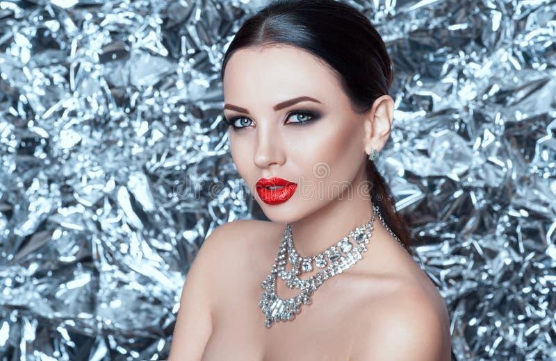 Retrato de la señora joven del encanto de lujo en el fondo de plata el noche del Año Nuevo foto de archivo