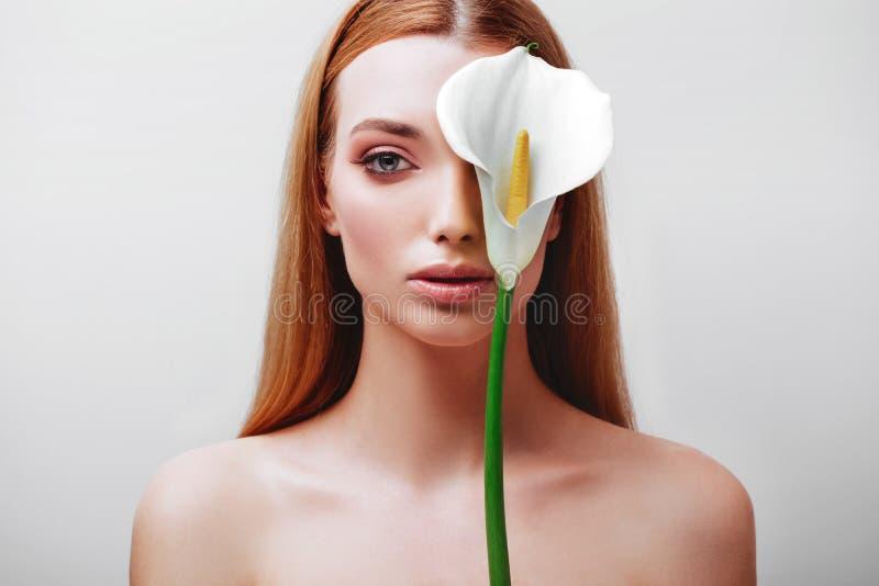 Retrato de la se?ora joven feliz del pelirrojo que mira fuera de las flores blancas fotografía de archivo
