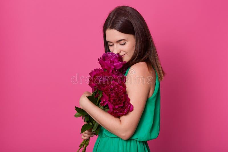 Retrato de la se?ora joven hermosa blanda que lleva en vestido verde casual, sosteniendo peon?as rosadas oscuras, olor de sensaci imagen de archivo