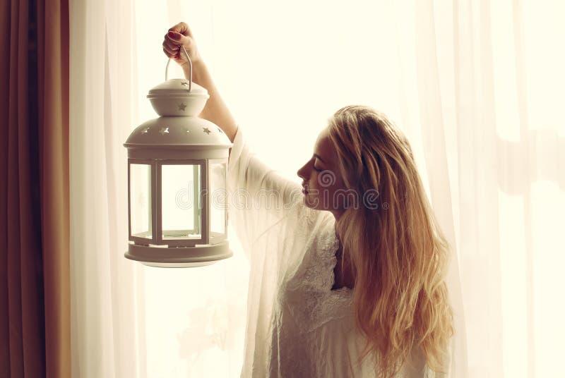 Retrato de la señora joven rubia hermosa que sostiene la antorcha ligera de la vela en la última hora de la tarde y que mira el e fotografía de archivo libre de regalías