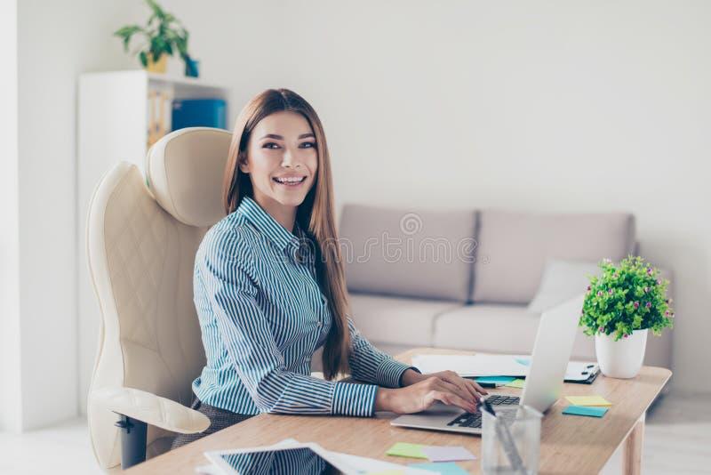 Retrato de la señora joven sonriente linda del negocio, sentándose en ella apagado fotos de archivo libres de regalías