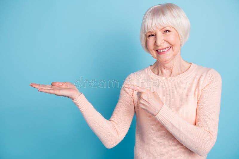 Retrato de la señora preciosa que señala su finger en el promo que lleva el suéter en colores pastel-coloreado aislado sobre fond imágenes de archivo libres de regalías