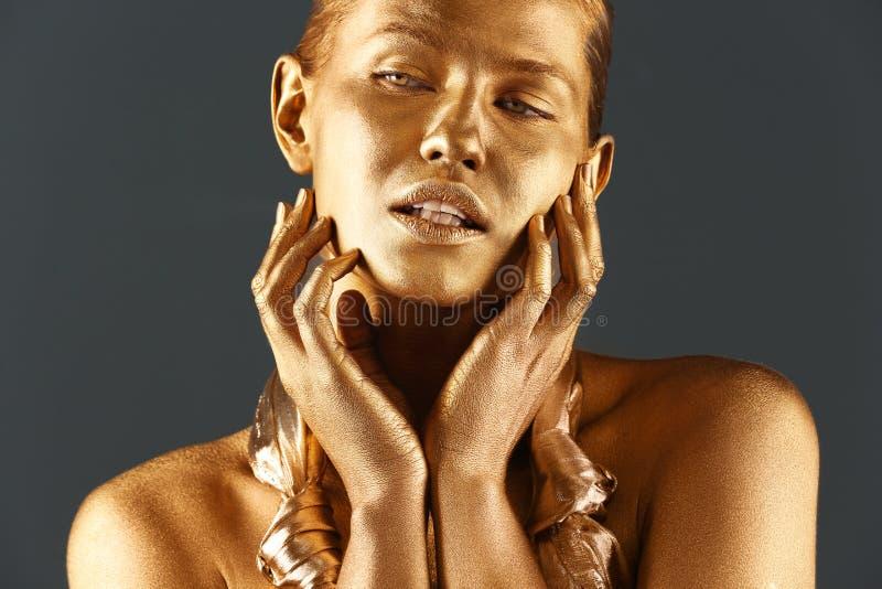 Retrato de la se?ora hermosa con la pintura del oro en piel contra fondo gris imagen de archivo libre de regalías