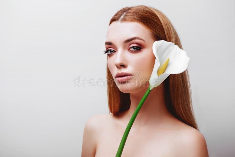 Retrato de la se?ora joven feliz del pelirrojo que mira fuera de las flores blancas foto de archivo libre de regalías