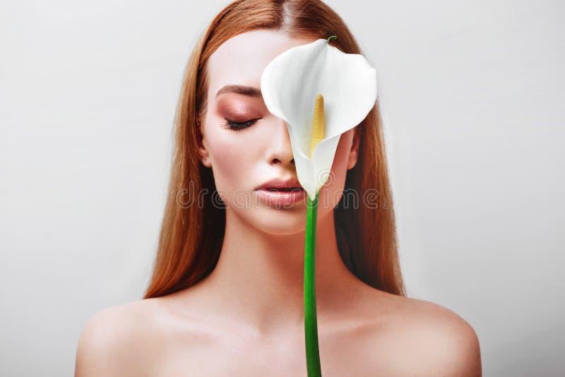 Retrato de la se?ora joven feliz del pelirrojo que mira fuera de las flores blancas imagen de archivo libre de regalías