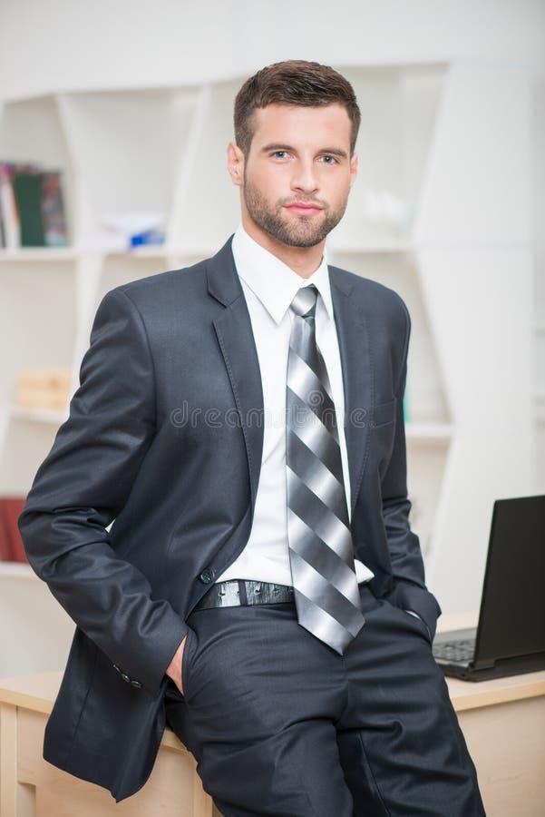 Retrato de la sentada confiada hermosa del hombre de negocios imagen de archivo libre de regalías