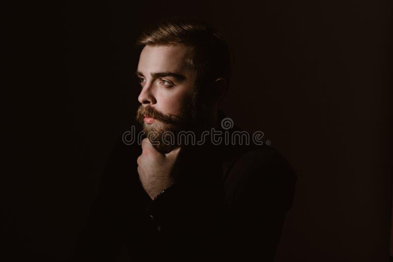 Retrato de la sepia de un hombre pensativo con una barba y un peinado elegante vestidos en la camisa negra en el fondo oscuro fotos de archivo