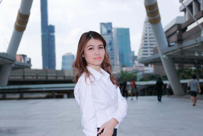 Retrato de la situación asiática joven atractiva de la empresaria en la acera y de mirar la cámara Pensamiento y negocio pensativ imagen de archivo