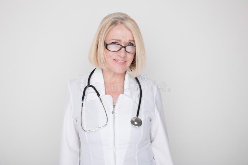 Retrato de la situación femenina profesional feliz del trabajador médico en un estudio con el estetoscopio en su cuello fotos de archivo libres de regalías