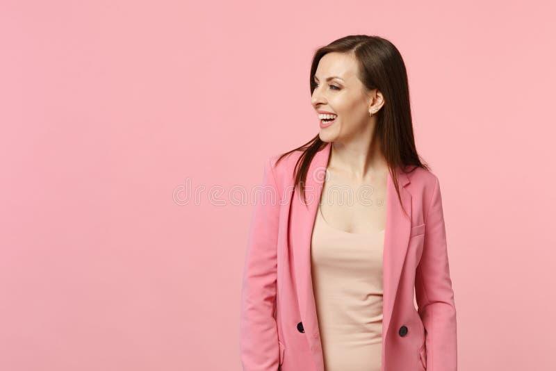Retrato de la situación de risa imponente y de parecer de la chaqueta de la mujer que lleva joven a un lado aislado en la pared r fotografía de archivo