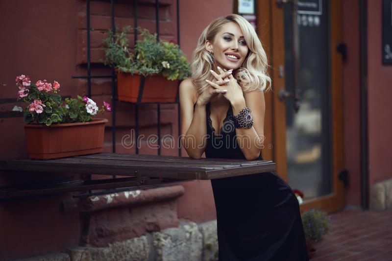 Retrato de la situación rubia sonriente hermosa de la mujer en el contador de la barra de la calle con las flores del pote en él imagenes de archivo