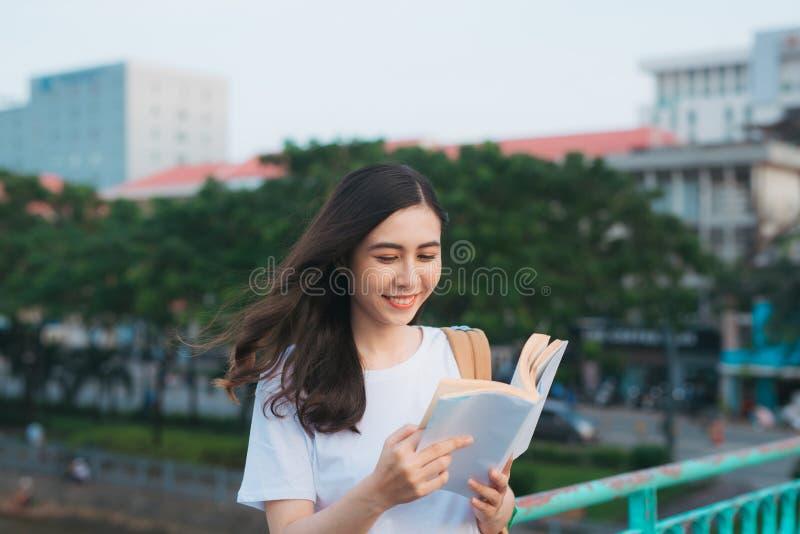Retrato de la situación vietnamita hermosa y de leer de la muchacha un libro en viento con el fondo de la ciudad de la falta de d fotografía de archivo
