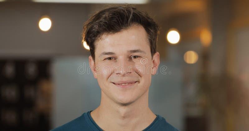 Retrato de la situaci?n acertada sonriente joven del hombre de negocios en oficina moderna Cierre para arriba foto de archivo