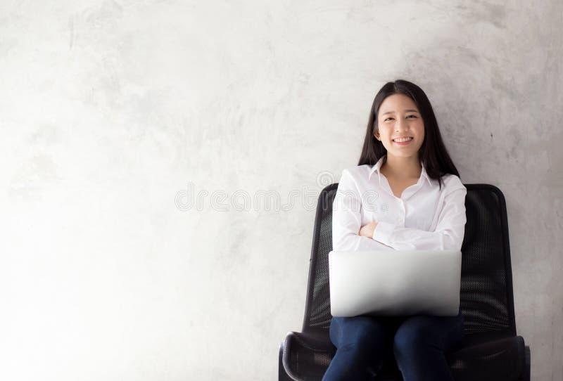 Retrato de la sonrisa asiática de la mujer joven usando el ordenador portátil en silla fotografía de archivo libre de regalías
