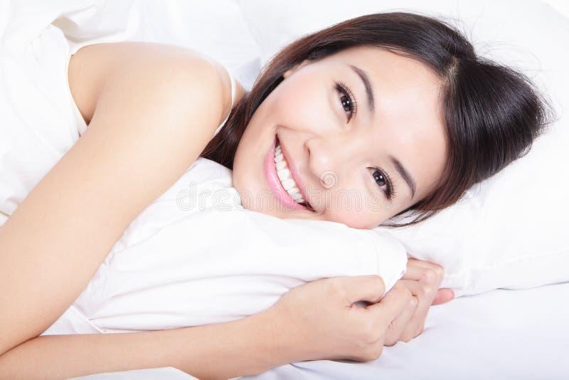 Retrato de la sonrisa de la mujer de la felicidad que miente en cama imagenes de archivo