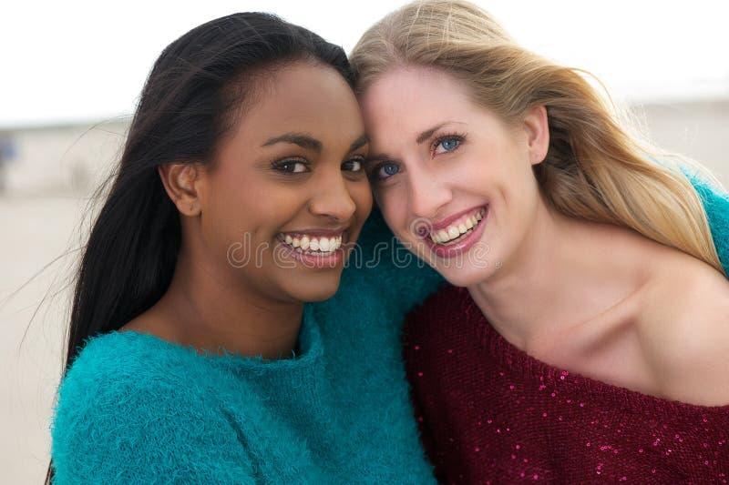Retrato de la sonrisa multicultural de dos muchachas imagen de archivo libre de regalías