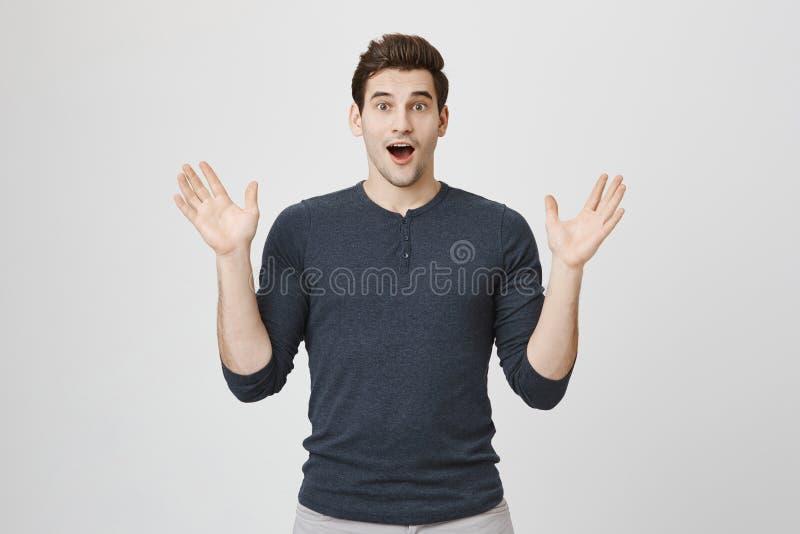 Retrato de la sorpresa apuesta y de la alegría de expresión modelo masculinas que aumentan sus manos, aislado sobre el fondo blan imagenes de archivo