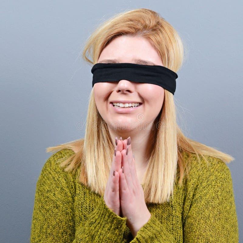 Retrato de la víctima del abuso y de la violencia doméstica vendada los ojos de contra fondo gris foto de archivo